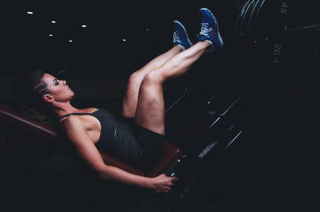 Eine Frau sitzt in der Beinpresse und trainiert ihre Beinmuskulatur. Der Hintergrund ist dunkel. Die Frau trägt eine schwarze Shorts, ein dunkel graues Top und blaue Turnschuhe.