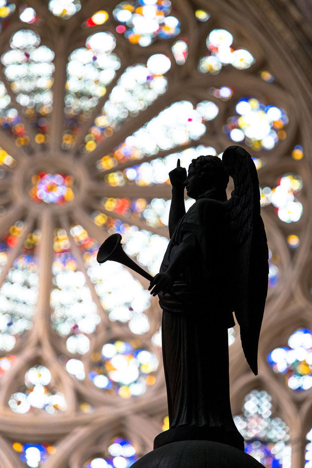 Angel statue with reminding hand in front of a the Cathedral Rosette Window, Metz, France, Europe