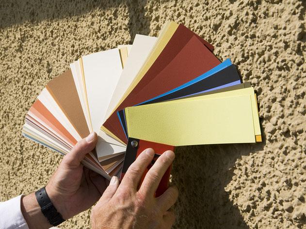 Für den Neuanstrich der Haussfassade wird die Farbe anhand eines Farbfächers ausgesucht.
