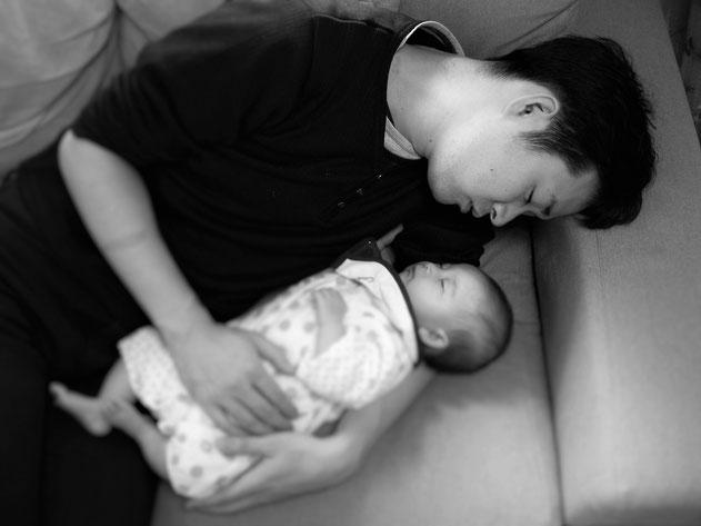 赤ちゃんを抱いて寝る院長。