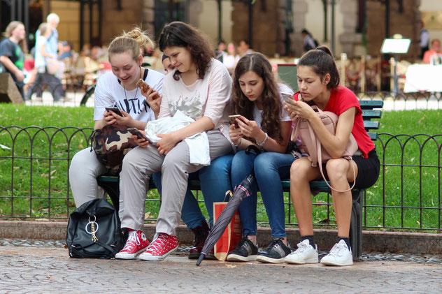 4-jeunes-adolescentes-sur-un-banc-qui-regardent-leur-smartphone