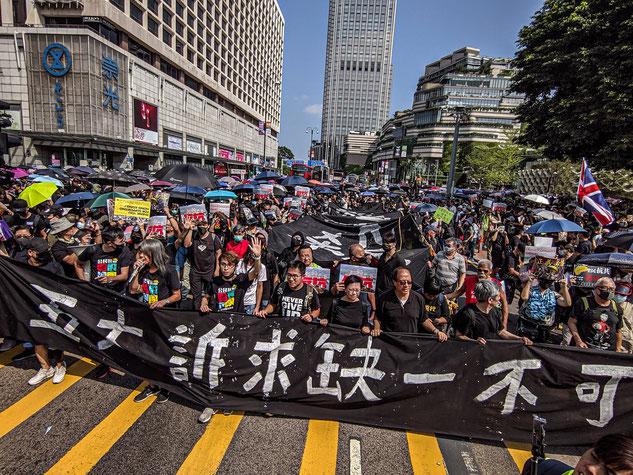 2019年10月、尖沙咀の抗議デモで「五大訴求缺一不可」の幕を掲げ更新する抗議デモ者。