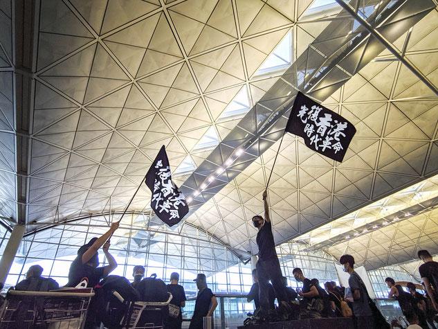 2019年8月、香港国際空港で「光復香港 時代革命」の旗を振りかざす抗議デモ者。
