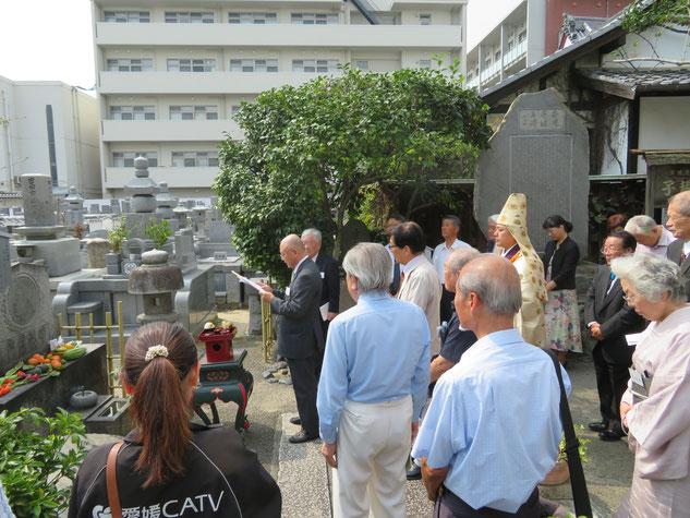正宗寺の子規墓前で会員の献句を詠む森慎吾経理部長と参拝者