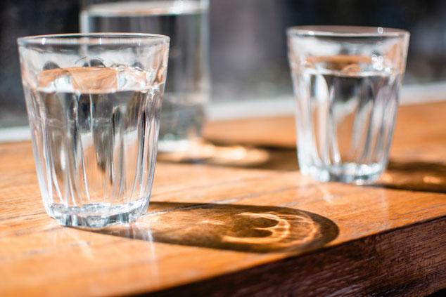 Auf einem Tisch stehen zwei Wasserglässer.