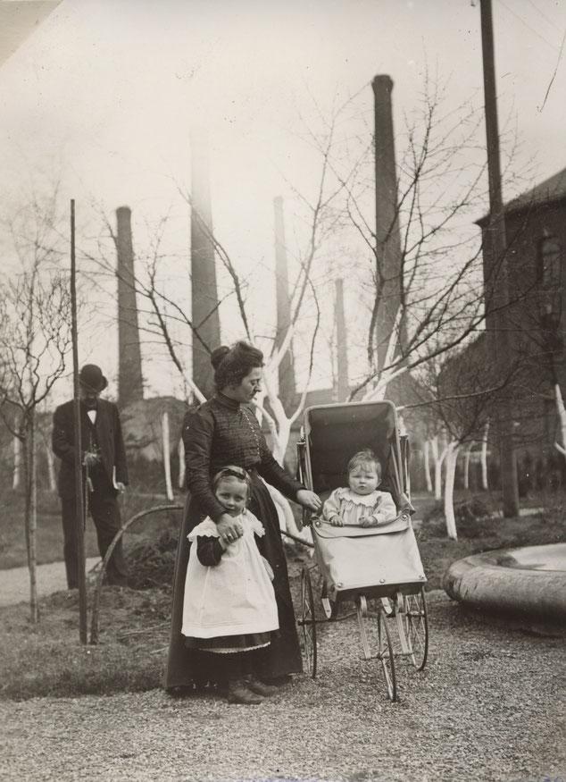 Blick vom Brunnen zur Fabrik, wahrscheinlich Babette (Frau von Erhard I) mit Else und Brunhilde um 1900, im Hintergrund Erhard?