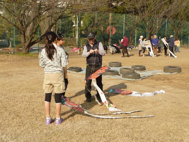 子ども広場でJJの会のメンバーに教わって凧揚げの準備