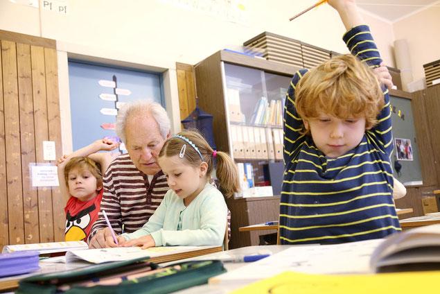 Senior mit jungen Schülerinnen im Klassenzimmer beim Lesen und Schreiben