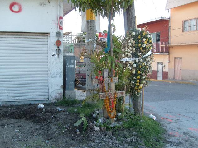 十字架が立てられた事件現場。壁には銃弾の跡が残る。