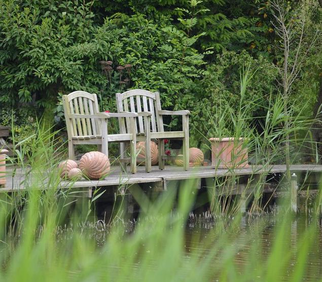 Bild: Garten mit Flair, 2 Liegestühle am Gartenteich mitten im Grün - Erholung pur