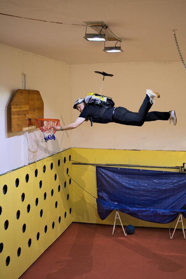 Immobilienfoto, Mann mit Hubschrauberrucksack bringt ein neues Basketballnetz an