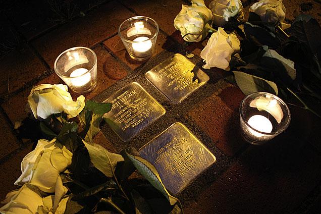 Rosen und Kerzen bleiben zurück an der Bundesstraße in Bad Rehburg nach der Verlegung der Stolpersteine für Familie Busack.