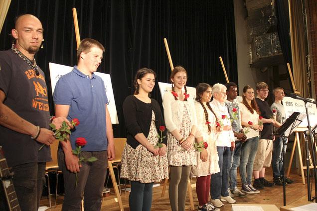 Rosen als Dank für eine berührende Vorstellung – und Annchen Heymer, deren eigene Geschichte vorgetragen wurde, in der Mitte der Jugendlichen.