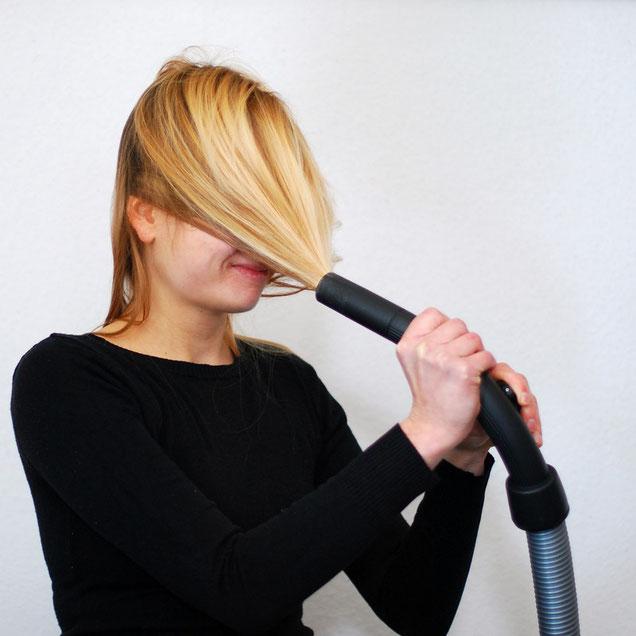Frau mit Haaren im Staubsaugerrüssel