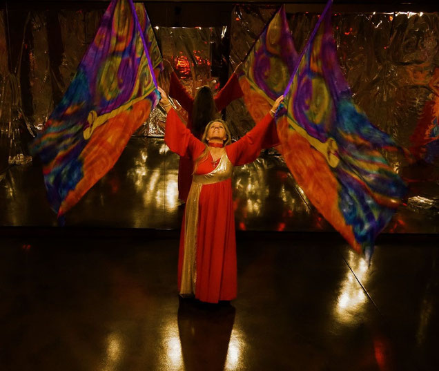Woman dancing with flags with gold trumpets and multicolored field.