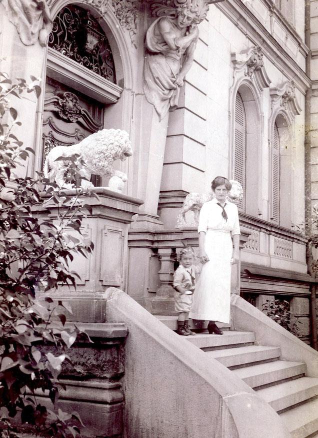 Elsa steht mit Sohn Werner am Eingang. Löwen säumen den Eingang. 1913
