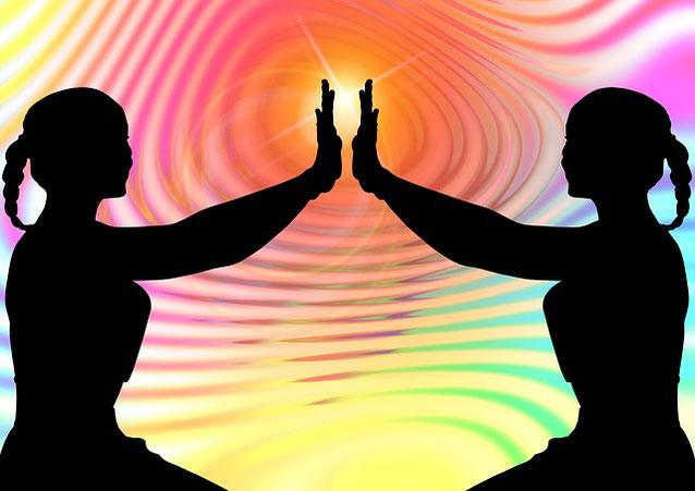 2 Menschen - Silouetten halten ihre Hände gegeneinander, bunter geringelter Hintergrund