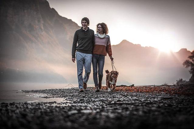 Verliebtes Paar läuft Hand in Hand mit Ihrem Aussie am Strand entlang im Hintergrund Berge und ein Sonnenaufgang fotografiert von der Ostschweizer Fotografin Monkeyjolie