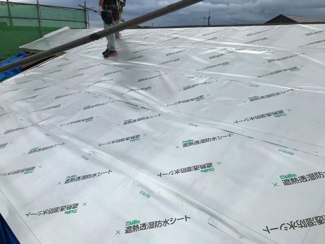 屋根の下地材の上に遮熱透湿防水シートを施工している様子
