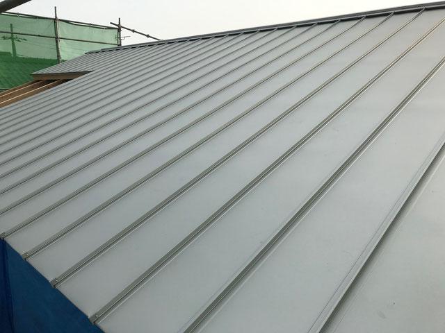 屋根の仕上げ材であるガルバリウム鋼板を施工している
