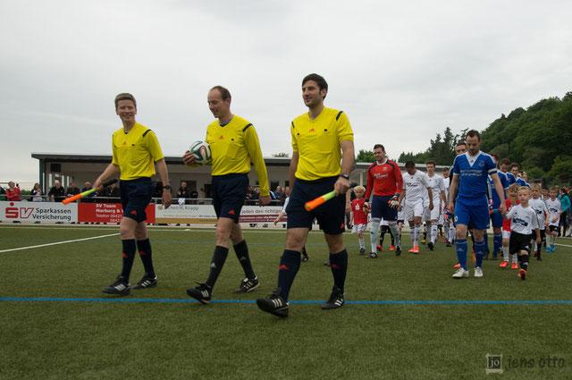 Referee Thorsten Eick mit seinen Assistenten Felix Ebert und Pirmin Mülot beim Einlaufen. Im Hintergrund begleiten unsere FSV- Kids beide Teams zum Mittelkreis.