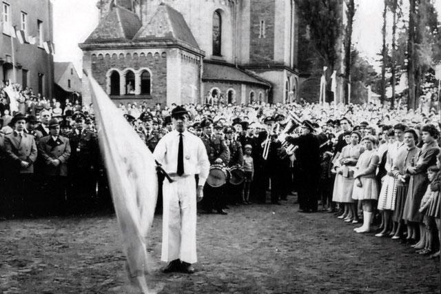 Fahnenschwenker Heinz Weyer vor dem Pastorat bei der Proklamation 1959. Quelle: SSB