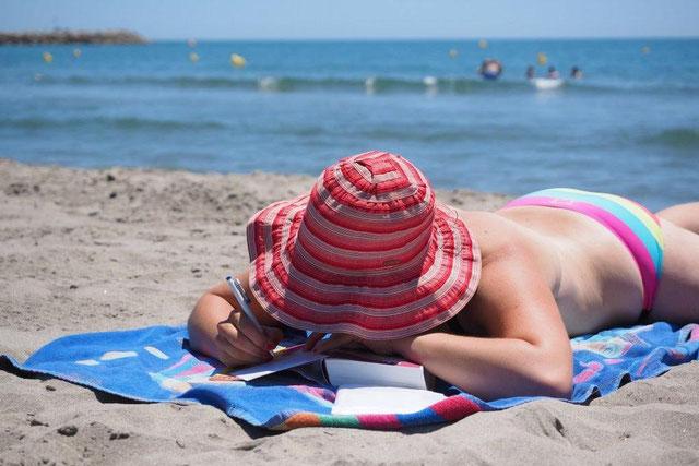 Frau im bunten Bikini mit rotem Sonnenhut liegt am Ostseestrand im Urlaub.