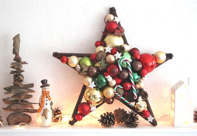 Stern aus Glaskugeln mit Zuckerstangen, Zapfen und einem fröhlichem Weihnachtsmanngesicht, in den Farben: rot - grün - gold - braun.