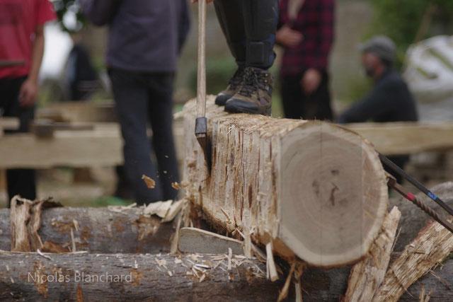 Façonnage à l'ancienne d'une bille de chêne lors de la réalisation d'une réplique d'une section de charpente de Notre-Dame de Paris par l'association des charpentiers sans frontières, en Septembre 2020 au château du Mesnil Geoffroy (Seine-Maritime)