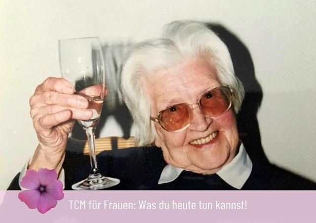 Omi mit weißen Haaren mit einem Glas Sekt in der Hand mit Brille  und Lächeln im Gesicht auf einer Feier und mit viel Freude zum Thema alt werden und dem Wasser-Element