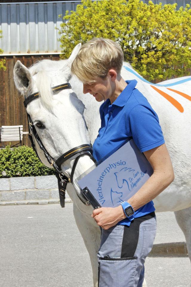 Dr. Laura Klingseisen-Bruun mit Logo-Mappe mit Pferd auf dem Physio-Tape aufgeklebt wurde