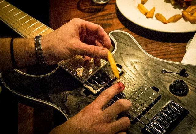 Leo's blutiger Finger mit einer Pommes daneben und seiner E-Gitarre