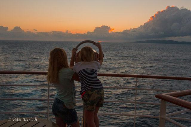 Zwei Mädchen beobachten über ein Fernglas auf einem Kreuzfahrtschiff, einen wunderbaren  Sonnenaufgang in der Karibik