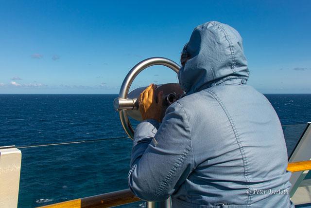 """Ein Mensch an einem Fernglas,  hält """"Ausschau"""", aber außer Weite und Wasser ist nichts zu sehen, nur die Weite des Atlantiks."""
