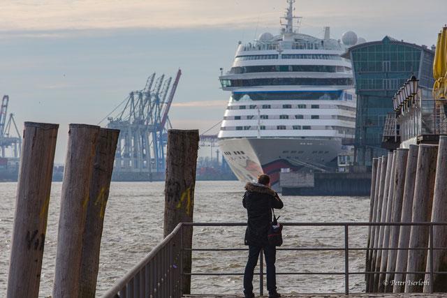 Auf der Fotografie ist ein Kreuzfahrtschiff der Reederei AIDA-Cruises zu sehen. Es wird der Bug des Schiffes durch einen Fotografen aufgenommen.