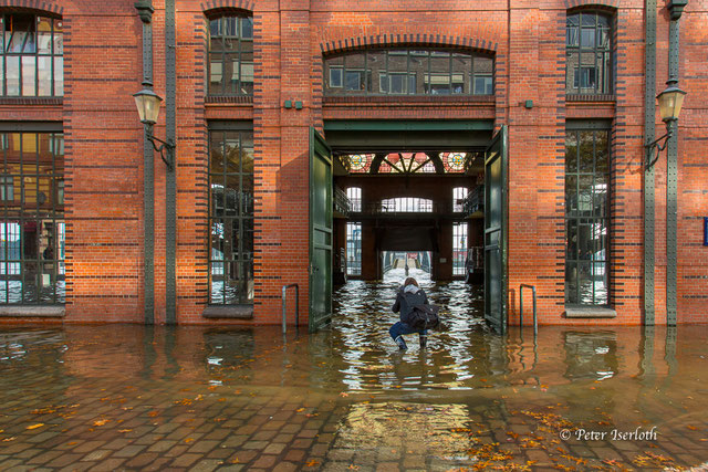 Die Hamburg Fischauktionshalle  im Hochwasser der Elbe, ein Fotograf hält diesen Moment mit seiner Kamera fest, Hamburg.