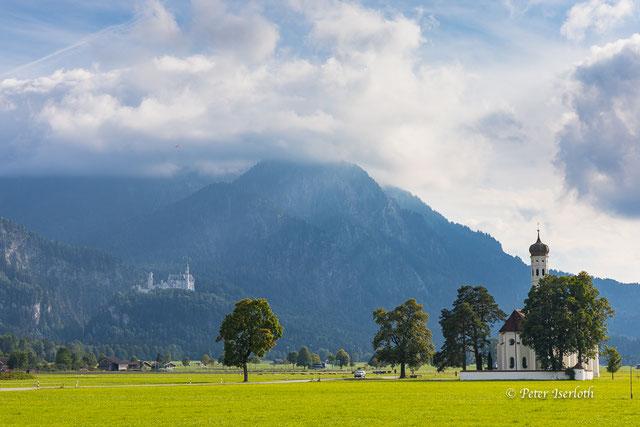 Landschaftsfotografie der Kirche St. Coleman Roman, im Vordergrund und dem Schloss Neu Schwanstein im Hintergrund.