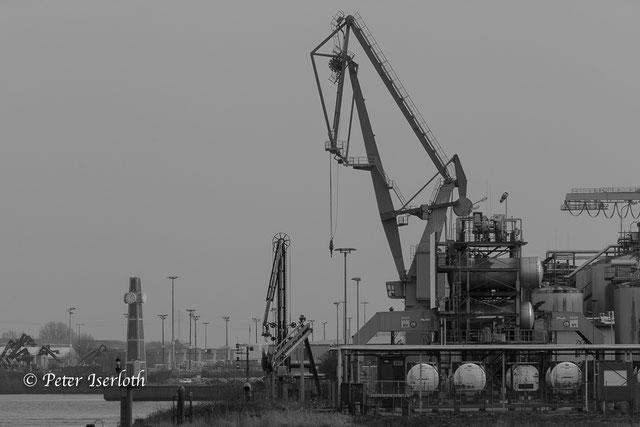 Das Bild zeigt ein Fotografie in Schwarzweiss von einem Hafenkran im Hamburger Hafen