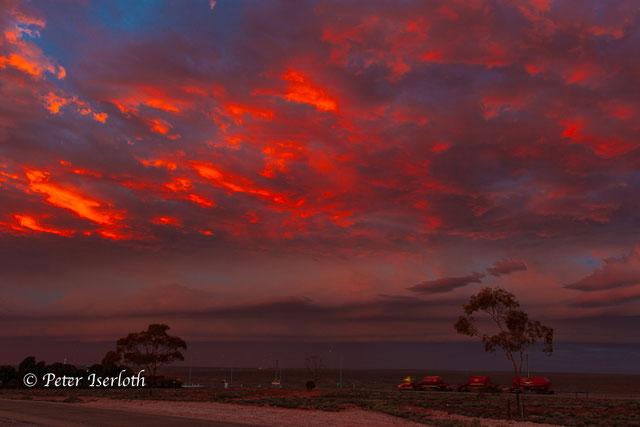 Sonnenaufgang im Outaback, von der aufgehenden Sonne werden ein paar Wolken grandios rotgefärbt.