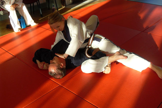 Sensei Faye locking up Sensei Rob on the floor