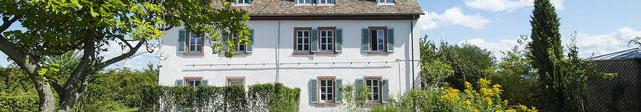 Das Künstlerhaus, 2 Etagen, weiß Fensterrahmen rotbraun, Fensterflügel grün, schräge Dachfenster. Eine Aufnahme im Sommer, ringsherum grün, im Vordergrund ein alter Baum.