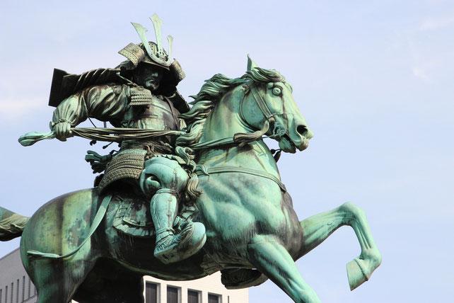 Eine Statue eines Samurai auf einem Pferd.