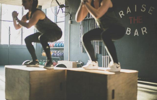 Zwei Frauen im Fitnessstudio machen Boxjumps. Beide sind in Schwarz gekleidet.