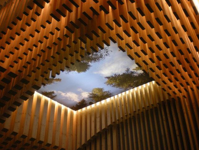Themenbezogener Messestand aus Holz. Beleuchteter Himmel im Digitaldruck mit Lichtakzenten in der Holzkonstruktion.