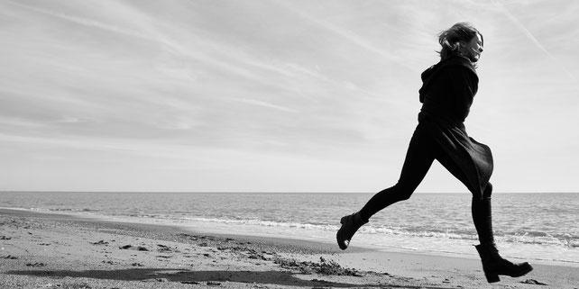 Frau rennt an einem einsamen Strand davon.