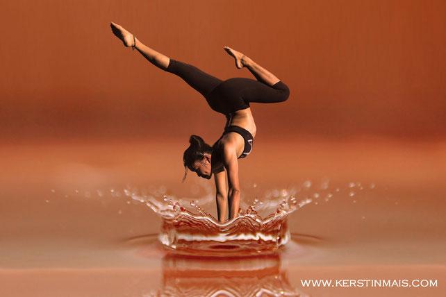 Frau macht Yoga Handstand im Wasser