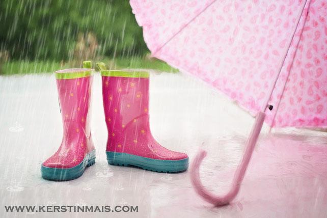 Rosa Gummistiefel und rosa Regenschirm im Regen