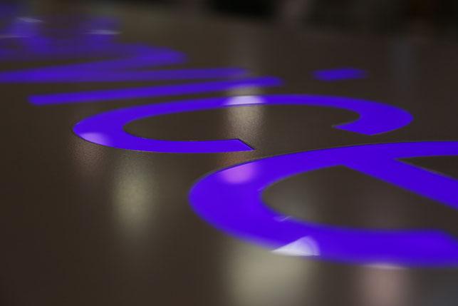 Aus beschichteter Alufront dekupierte Schrift mit Plexiglas hinterlegt oder bündig eingesetzt und mit LED hinterleuchtet
