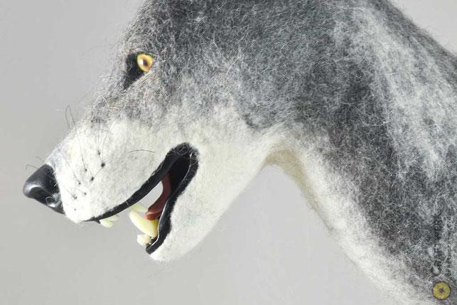Gefilzter Wolfskopf mit gefletchten Zähne und gelben Augen