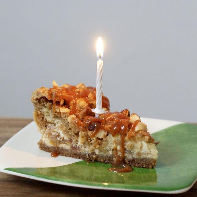 Apfel-Käsekuchen mit Streuseln und Karamell mit Geburtstagskerze